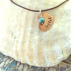 "Copper ""Joyful Heart"" charm with leather cord."